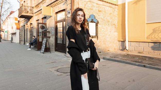 Glückliches vorbildliches mädchen im mode-outfit geht auf der straße