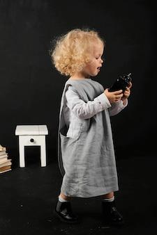 Glückliches vorschulmädchen mit bücher, kugel und uhr auf einem schwarzen hintergrund