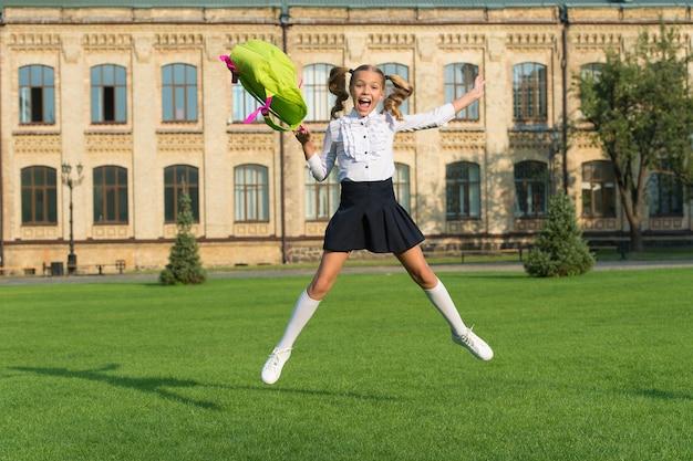 Glückliches vorschulmädchen mit rucksack. springen auf dem schulhof. zurück zur schule. kind in uniform feiern ende des jahres. konzept der bildung. kindheitsglück. glückliches mädchen, fühlen sie sich frei.