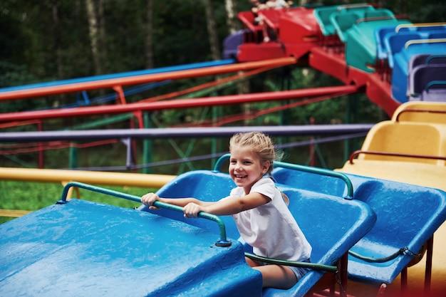 Glückliches weibliches kind hat tagsüber spaß auf einer achterbahn im park.