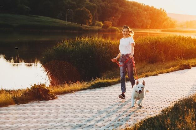 Glückliches weibliches laufen mit weißem hund an der leine während des gehens am parkweg mit wasser und gras mit bäumen auf hintergrundbeleuchtetem hintergrund am abend