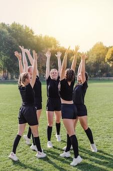 Glückliches weibliches team, das hände anhebt