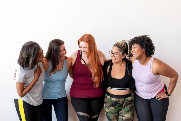 Glückliches weibliches trainingsteam im fitnessstudio