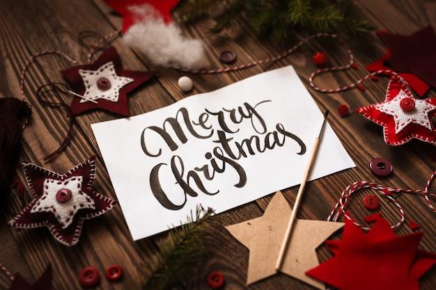 Glückliches weihnachtsbeschriftungsaufschrift auf papier auf hölzernem