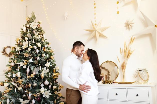 Glückliches weihnachtskonzept, verliebtes paar, das durch den weihnachtsbaum umarmt und küsst