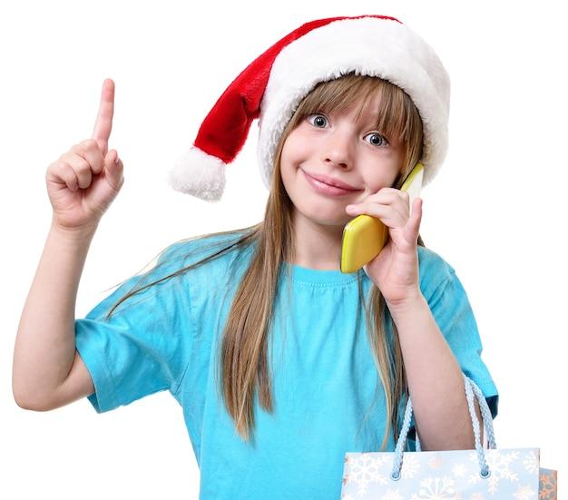 Glückliches weihnachtsmädchen halten große einkaufstaschen lokalisiert auf weiß.
