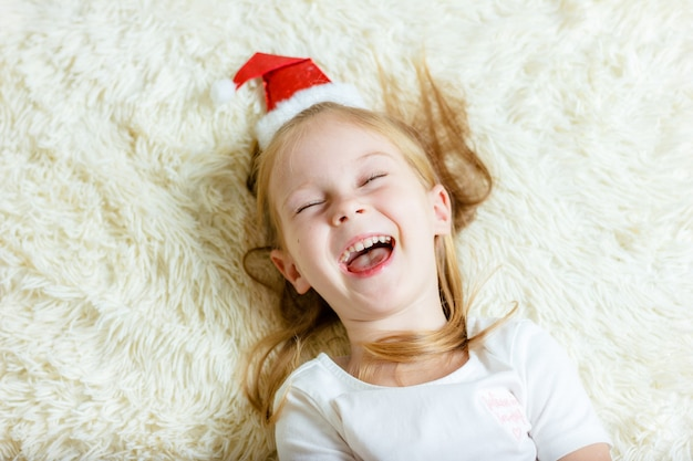 Glückliches weihnachtsmädchen liegt auf einer decke und lacht.