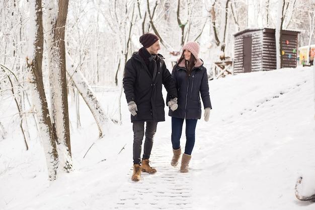 Glückliches weihnachtspaar in der liebe, die im kalten winterwinterwald kalt geht