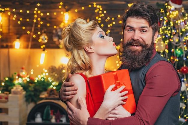 Glückliches weihnachtspaar küsst und umarmt mit roter geschenkbox