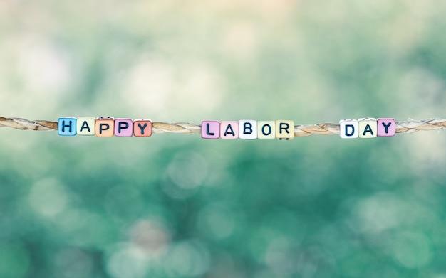Glückliches werktagswort, das durch seil mit schönem grünem natur-bokeh hintergrund hängt