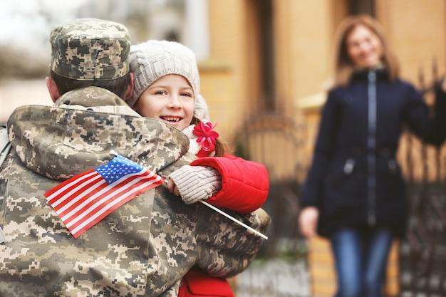 Glückliches wiedersehen des soldaten mit der familie im freien