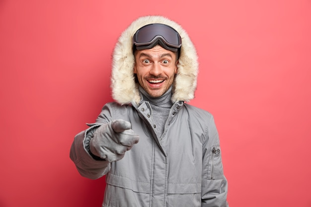 Glückliches winterzeitkonzept. fröhlicher europäischer mann in oberbekleidung zeigt direkt mit fröhlichem ausdruck etwas sehr angenehmes an.