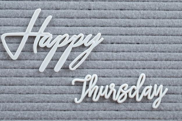 Glückliches wochentagsplakat geschrieben mit buchstabensymbolen auf dem grauen gewebe