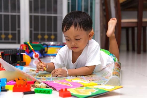 Glückliches zeichnen und lesen des kleinen jungen