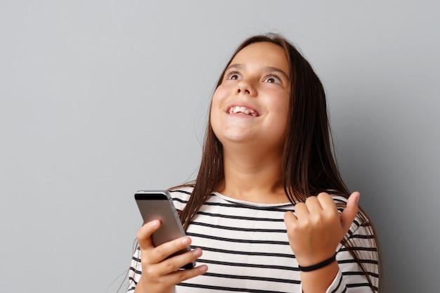 Glückliches zufälliges kleines mädchen, das ihr telefon über grauem hintergrund betrachtet