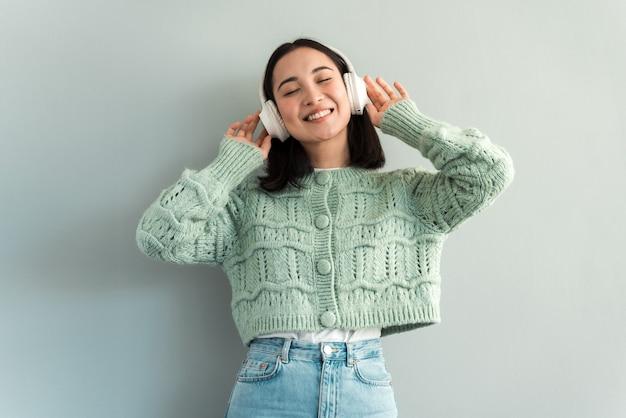 Glückliches zufriedenes mädchen, das ihre lieblingsmusik mit kopfhörern steht und hört. ihre augen schlossen sich und sie lächelte zähnefletschend. indoor-studioaufnahme auf grauem hintergrund isoliert