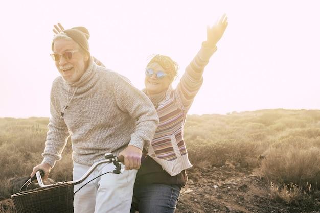 Glücks- und freiheitskonzept ohne altersgrenze mit altem ehepaar, das lächelt und viel spaß zusammen auf einem fahrrad bei outdoor-freizeitaktivitäten hat - jugendliche und verspielte menschen im ruhestand