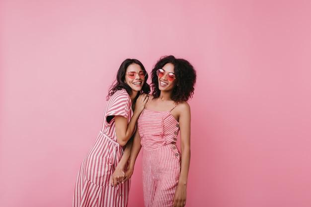 Glückselige afrikanische frau im trendigen sommeroutfit, das mit freund genießt. verträumte mädchen in rosa kleidern, die spaß haben.