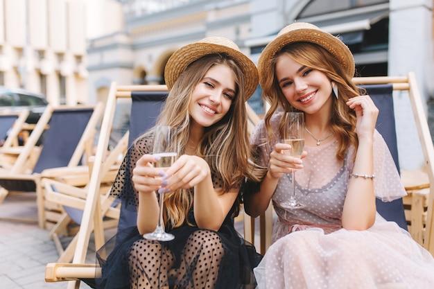 Glückselige blonde mädchen in neuen stilvollen kleidern und sommerhüten genießen urlaub und trinken kaltes getränk