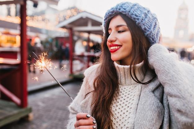 Glückselige braunhaarige frau mit aufrichtigem lächeln, die weihnachtsferien genießt und mit wunderkerze aufwirft. charmantes mädchen im weichen blauen hut, der bengalisches licht auf der straße hält.