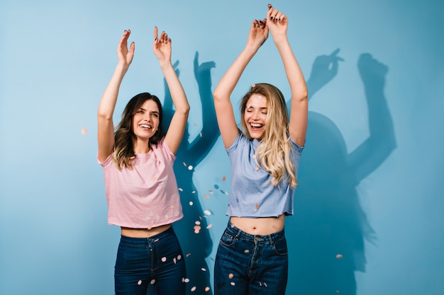Glückselige damen tanzen mit erhobenen händen