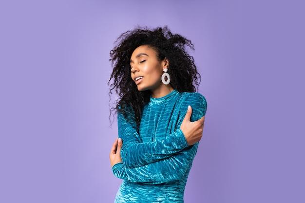 Glückselige frau des afroamerikaners mit geschlossenen augen im samtkleid mit gewelltem haar, das aufwirft. porträt im modestil.