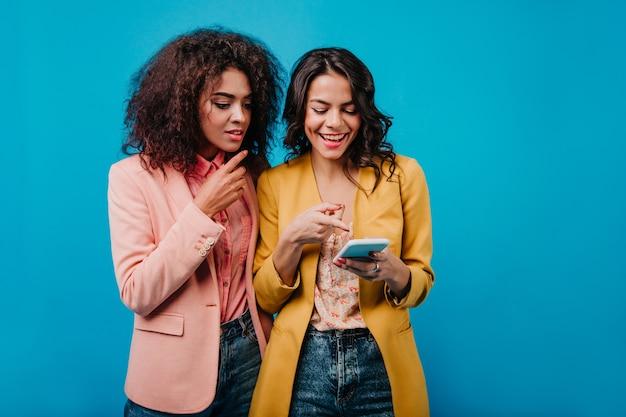 Glückselige frau, die neues smartphone zeigt