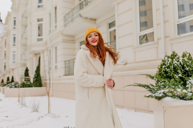 Glückselige frau im langen mantel, der im dezember aufwirft. winterporträt des ingwermädchens mit fröhlichem lächeln.
