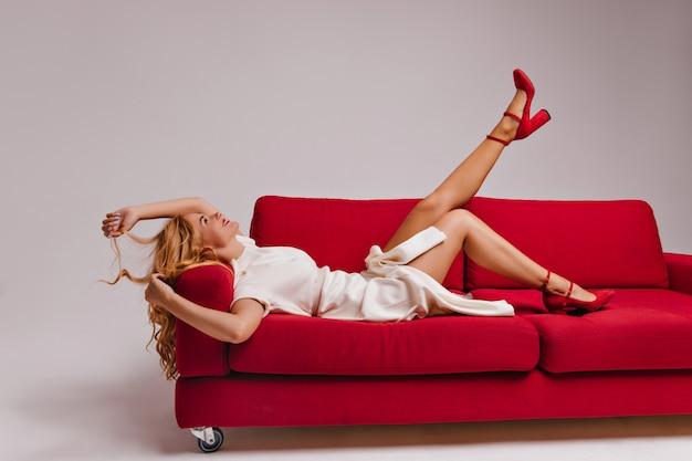 Glückselige frau in den trendigen schuhen mit hohen absätzen, die auf dem sofa liegen. lachendes frohes blondes mädchen, das auf couch posiert