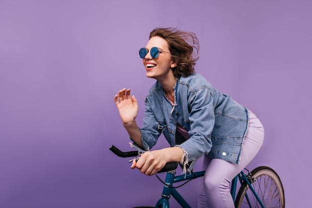 Glückselige frau in der freizeitjacke, die auf fahrrad aufwirft. emotionales kurzhaariges mädchen in funkelnden gläsern, die auf fahrrad fahren.