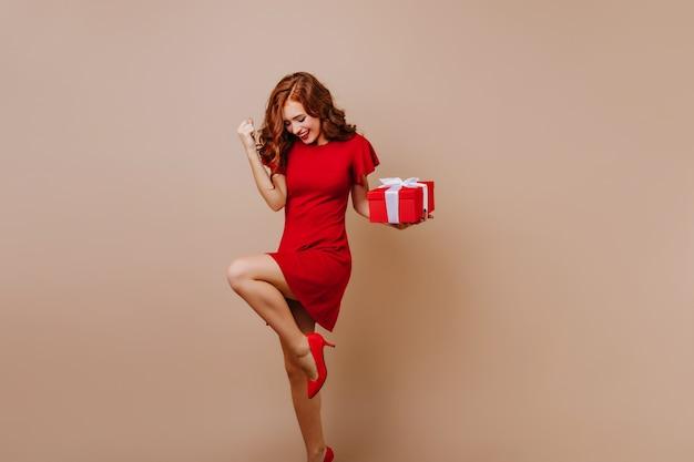 Glückselige frau in schuhen mit hohen absätzen, die an der weihnachtsfeier tanzen. freudiges geburtstagskind, das glück ausdrückt.
