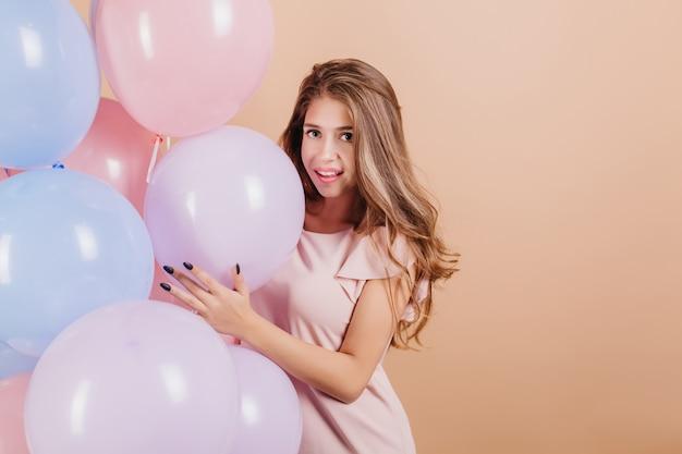 Glückselige frau mit dem langen gewellten haar, das mit bunten heliumballons aufwirft
