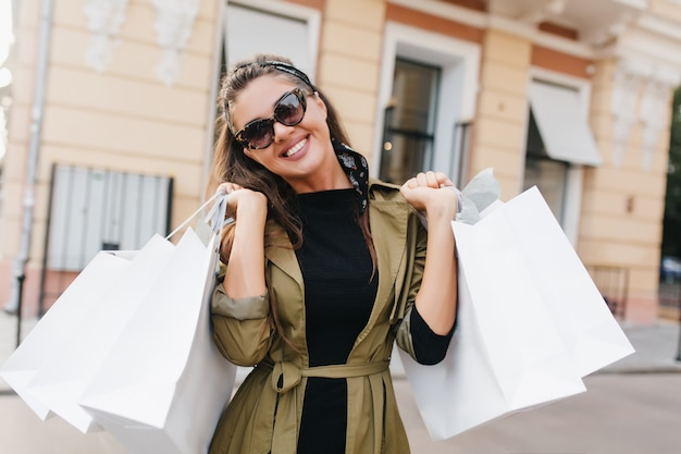 Glückselige hispanische fashionista-frau, die nach dem einkaufen mit aufrichtigem lächeln aufwirft