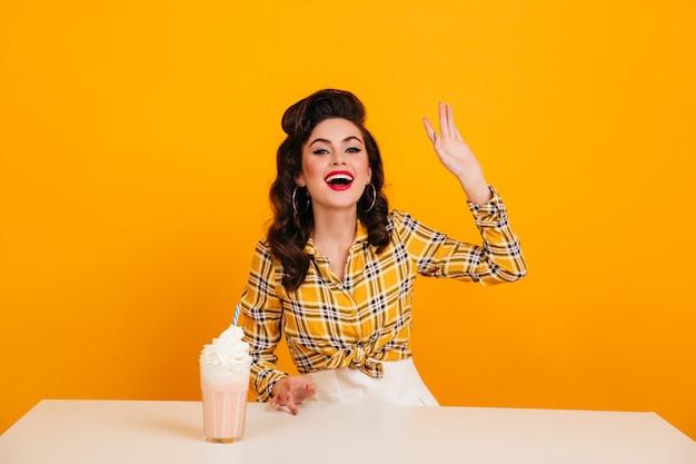 Glückselige junge frau mit milchshake, die auf gelbem hintergrund lacht. studioaufnahme des positiven pinup-mädchens im hellen karierten hemd.