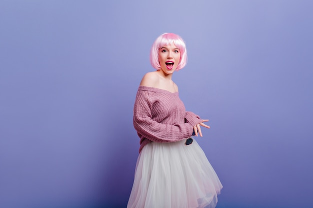 Glückselige junge frau trägt weißen rock und rosa perücke, die mit glücklichem gesichtsausdruck posiert. hübsches weibliches model im modischen peruke, das spaß hat