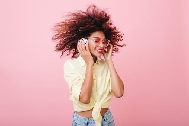 Glückselige mulattin im gelben baumwollhemd, das im rosa raum herumalbert. erfreutes schwarzes mädchen mit lockiger brauner frisur, die weiße kopfhörer berührt und lacht.