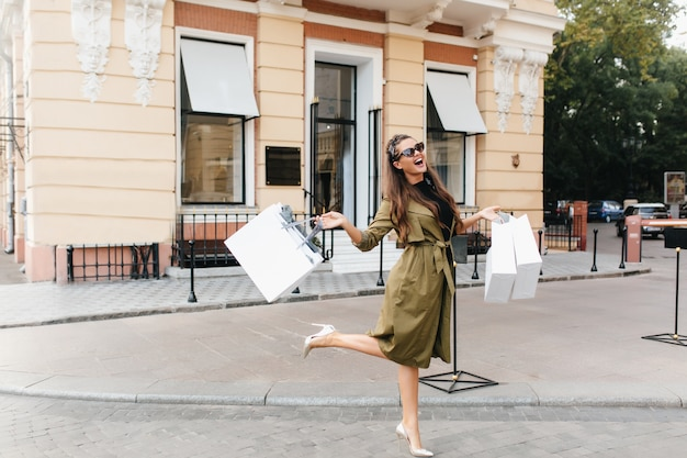 Glückselige shopaholic frau, die auf der straße mit lächeln tanzt
