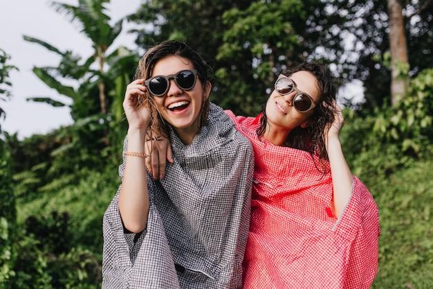 Glückselige weibliche modelle, die positive emotionen im freien ausdrücken. attraktive frauen im regenmantel, die auf exotischem dschungel umarmen.