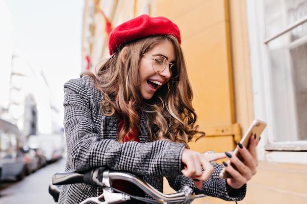 Glückselige weiße frau mit brünettem haar, das telefonbildschirm mit lächeln auf straßenhintergrund betrachtet