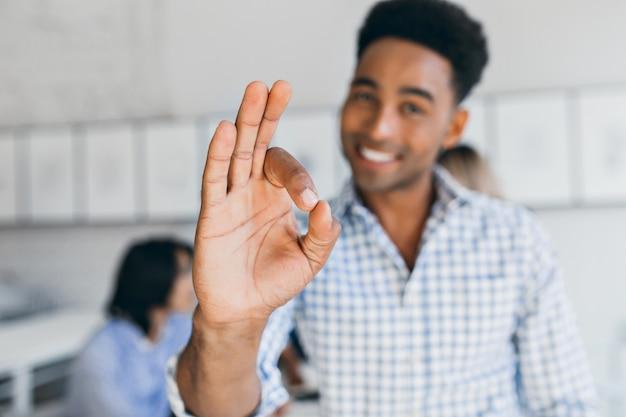 Glückseliger büroangestellter, der spaß mit kollegen hat und gutes zeichen zeigt. innenporträt des lachenden schwarzen jungen mannes, der in der internationalen gesellschaft mit seiner hand im fokus arbeitet.