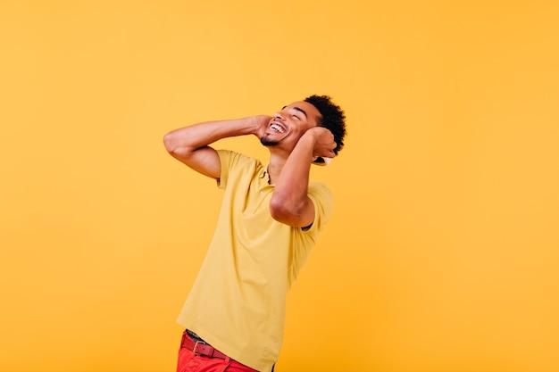 Glückseliger junger mann im trendigen hellen t-shirt lachend. innenfoto des emotionalen afrikanischen kerls, der mit geschlossenen augen lächelt.
