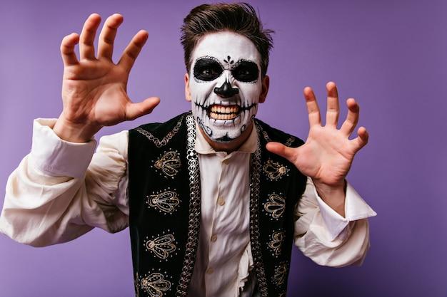 Glückseliger kaukasischer kerl, der spaß in halloween hat. lustiger junger mann mit kurzem haarschnitt, der im zombiekostüm aufwirft.