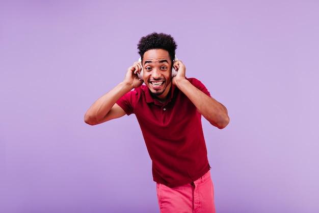 Glückseliger lockiger lustiger mann, der schaut. afrikanischer mann in roten kleidern, die in weißen kopfhörern aufwerfen.