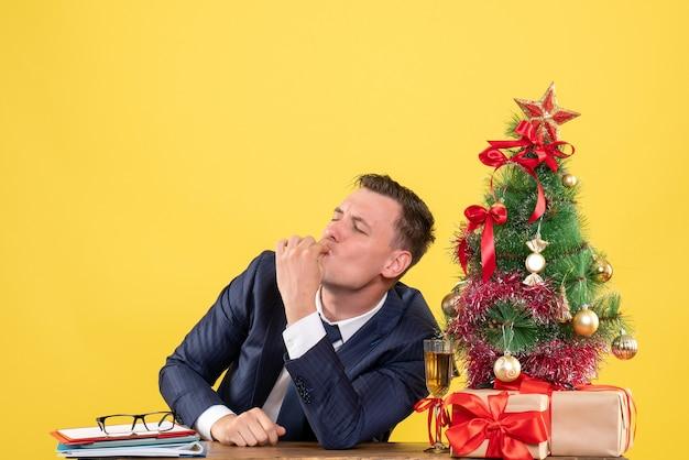 Glückseliger mann der vorderansicht, der cheff-kussgeste macht, die am tisch nahe weihnachtsbaum und geschenken auf gelbem hintergrund sitzt