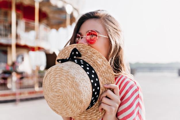 Glückseliges blondes mädchen, das gesicht mit strohhut bedeckt, während es im sommertag aufwirft. foto im freien der glücklichen jungen frau in der rosa sonnenbrille, die im vergnügungspark ruht.