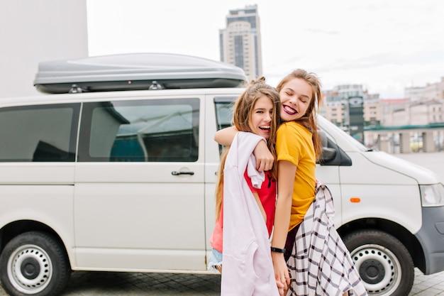 Glückseliges braunhaariges mädchen mit glücklichem lächeln, das ihre beste freundin mit trendiger frisur umarmt