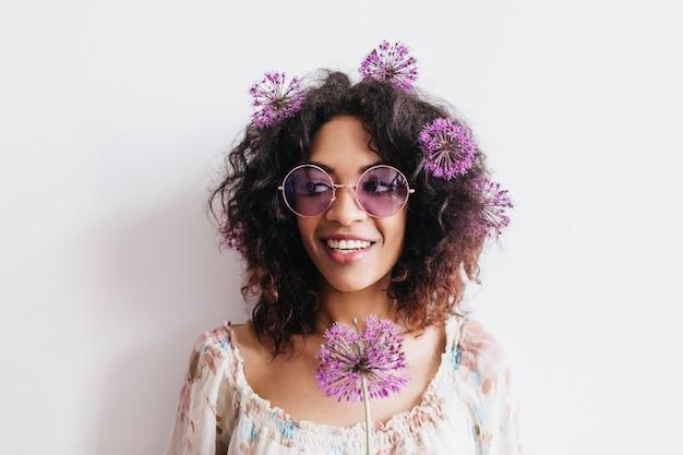 Glückseliges brünettes mädchen in den trendigen gläsern, die mit blumen im haar aufwerfen. curly afrikanische frau mit lila allium stehend.