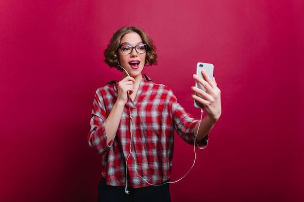 Glückseliges junges weibliches modell trägt eine brille und ein kariertes hemd, das selfie auf rotweinwand macht. glückliches kurzhaariges mädchen mit telefon, das spaß in der freizeit hat.