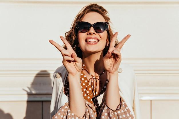 Glückseliges kurzhaariges mädchen, das an sonnigem tag lacht. porträt der sorglosen brünetten frau in der schwarzen sonnenbrille, die mit friedenszeichen aufwirft.