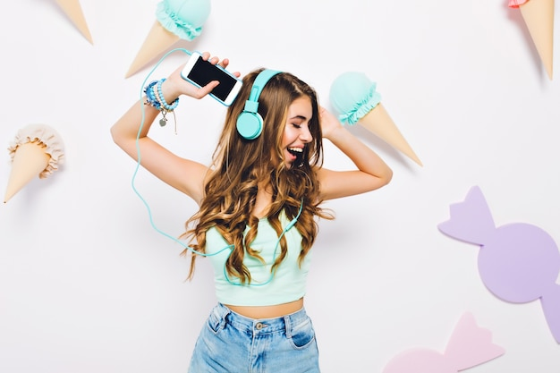 Glückseliges lockiges mädchen in den großen blauen kopfhörern, die an der wand tanzen, verziert mit lila süßigkeiten und eiscreme. porträt der fröhlichen jungen frau, die spaß hat und musik mit geschlossenen augen genießt.